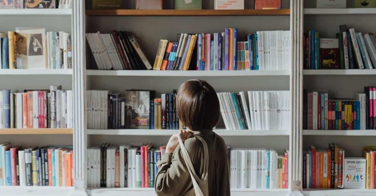 A person reading a book in front of a bookshelf