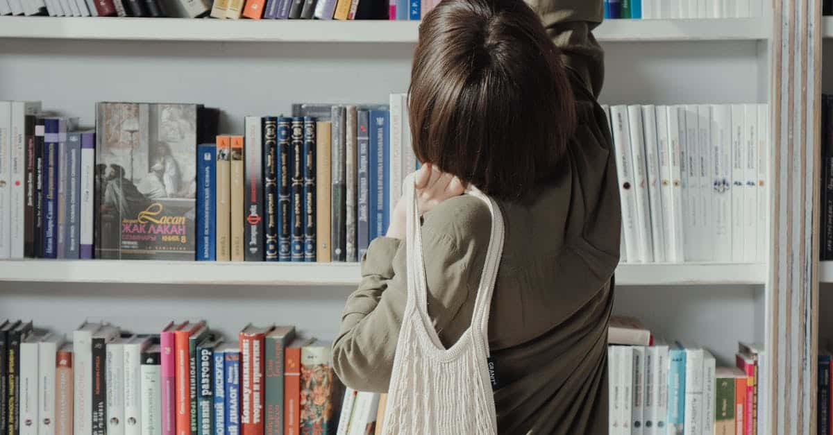 A person standing in front of a book shelf